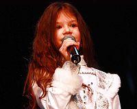 Una mujer joven que canta en un micrófono delante de un fondo negro, que llevaba una blusa blanca.
