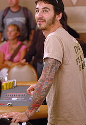 A man with tattoos covering his left arm looks to his right while playing poker.