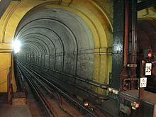A narrow railway tunnel with a single railway track, lit by a bright white light
