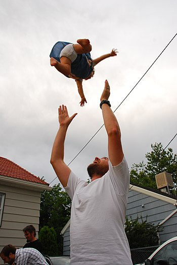 a baby being tossed up by a man