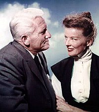 Hepburn is sitting with Spencer Tracy, she age 50 and he age 57, and they are smiling at each other.