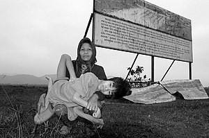 Herbicidal warfare - Kan Lay, 55 years old, and her son, Ke Van Bec, 14 years old, physically and mentally handicapped, pose in front of the billboard denouncing the Operation Ranch Hand.