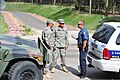 U.S. Army Sgt. Bobi Limon, left, and Spc. Joshua Dietrich, center, with the Colorado Army National Guard, coordinate with a police officer as they provide security for evacuated homes at a checkpoint near 130613-Z-WF656-018.jpg