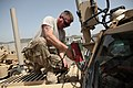 U.S. Navy Construction Mechanic 1st Class William Cook, assigned to Construction Battalion Maintenance Unit 202, attached to the Khost Provincial Reconstruction Team, unbolts the windshield from a Cougar H 6x6 120811-A-PO167-009.jpg