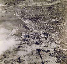 Black and white aerial photograph of a city. Part of the city at the bottom of the photograph has been completely destroyed.