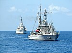 USNS Grasp (T-ARS-51) tows USS Des Moines (CA-134) to the scrapyard, in October 2006.jpg
