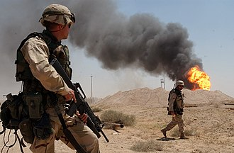 Foreign policy of the United States - A U.S. soldier stands guard duty near a burning oil well in the Rumaila oil field, Iraq, April 2003