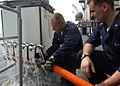 US Navy 050105-N-4383M-043 Hull Maintenance Technician 1st Class Jason Curry, left, and Hull Maintenance Technician 3rd Class Branden Stone, test a fresh water distribution manifold.jpg