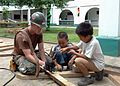 US Navy 060606-N-3532C-047 Builder 2nd Class Shane Murray assigned to Naval Mobile Construction Battalion Four Zero (NMCB-40), receives help from some children to build a picnic table for the Sulu Provincial Hospital.jpg