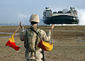 US Navy 070204-N-6482W-032 Boatswain's Mate Seaman Paul Wibright, assigned to Beach Master Unit Two (BMU-2) embarked aboard the amphibious assault ship USS Bataan (LHD 5), directs a Landing Craft Air Cushion (LCAC) to the beach.jpg