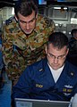 US Navy 070617-N-4124C-016 Lt. Richard N. Bean, meteorology and ocean officer for the Royal Australian Navy, looks over the shoulder of Chief Warrant Officer 2 Jon P. Stacy, force protection officer for Amphibious Squadron 11,.jpg
