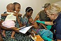 US Navy 070813-N-4954I-049 Ensign Stacy Syrstad, a nurse practitioner from Naval Medical Center San Diego, calms a child after a vaccination at a medical civil-assistance program (MEDCAP) at Ileg Clinic near Madang.jpg
