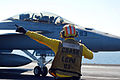 US Navy 100118-N-3589B-011 A flight deck director signals to an F-A-18C Hornet assigned to the Sidewinders of Strike Fighter Squadron (VFA) 86.jpg