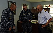 US Navy 100824-N-9643W-390 Capt. Michael Jacobsen, center, Capt. Kurt Hedberg, left, and the commanding officer of the Barbados Defense Force look at old photos