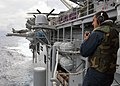 US Navy 110304-N-ZS026-004 Gunner's Mate 3rd Class Adam Torres, from Oxnard, Calif., communicates through a sound-powered phone while standing watc.jpg