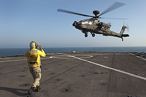 US Navy 120128-N-KS651-305 A Sailor signals a helicopter to land on the flight deck of USS Pearl Harbor.jpg