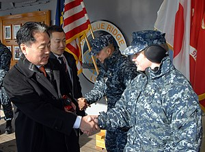 US Navy 120204-N-DX698-108 A Hokkaido Prefectural Assembly Member peaks with Sailors.jpg