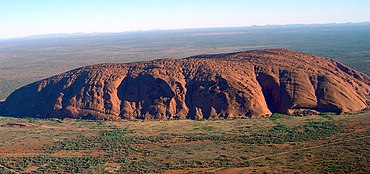 Uluru – a long, low mountain against a flat Australian plain