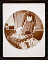 Unidentified Photographer - Baby in carriage, woman standing behind - Google Art Project.jpg