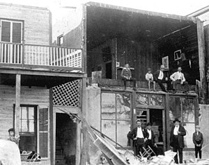 1896 Cedar Keys hurricane - Storm victims pose with damaged houses on Cedar Key.
