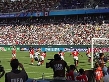 A soccer game between the United States and Canada, seen from behind one of the goals.