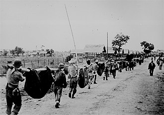Bataan Death March - A burial detail of American and Filipino prisoners of war uses improvised litters to carry fallen comrades at Camp O'Donnell, Capas, Tarlac, 1942, following the Bataan Death March.