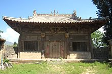 The Main Hall of Yanqing Temple. There is blue sky behind the hall. There is one door opening to a grassy courtyard