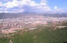 Aerial view of a city, surrounded mostly by desert. In the foreground and background are hills with sparse vegetation.
