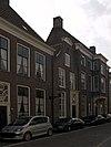 foto van Pand met door gebogen fronton gedekte bakstenen klokgevel met in pilasteromlijsting gevatte voordeur en bovenlicht