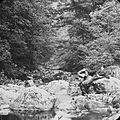 """Man seated on rocks, by a river and surrounded by woodland in an unidentified location""? (10704700994).jpg"
