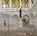 (Great Hall. View of grand staircase and bronze statue of female figure on newel post holding a torch of electric light, with bust of George Washington at left. Library of Congress Thomas Jefferson Building, Washington, D.C.) (LOC).jpg