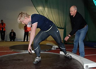National Sports Centre Papendal - Coach Dieter Kollark giving instruction to German athlete Petra Lammert on shot put training, within the indoor facilities at the National Sports Centre Papendal