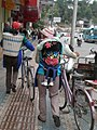 2 women with bicyles on Minzhu Road, Lijiang.JPG