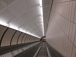 Looking down a bank of two escalators in a semi-elliptical passage lit by fluorescent light strips above, generally white with some yellow paneling on the walls. There are no people on the escalator. The wall on the right-hand side is flat and contains a vertical tiling pattern, while the wall on the left-hand side is curved with tiles patterned diagonally and parallel to the escalator.