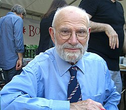 A grey-haired Oliver Sacks with glasses, a beard and a blue shirt with three people in the background