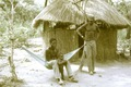 ASC Leiden - Coutinho Collection - D 21 - Hermangono, Guinea-Bissau - Soldiers in front of a hut with a child - 1974.tif