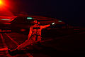 A catapult and arresting gear officer signals for the night launch of an aircraft from the aircraft carrier USS John C. Stennis (CVN 74) as the ship operates at sea on Jan 130131-N-OY799-176.jpg