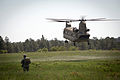 """A jumpmaster with the 82nd Airborne Division's 1st Brigade Combat Team waits for a CH47 Chinook helicopter to land so that he can load his """"chalk"""" of paratroopers aboard for a training jump in 2013.jpg"""
