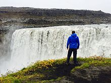A man is standing on the left bank of Dettifoss waterfall.jpg