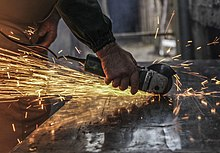 Bright sparks fly as a man grinds a piece of metal