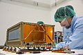 A young man screws bolts in a newly made box satellite.jpg