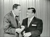 two men stand in front of a curtain speaking to each other