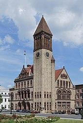 Un edificio in mattoni marrone e marrone chiaro con finiture marrone scuro.  L'edificio ha un alto campanile all'angolo più vicino.