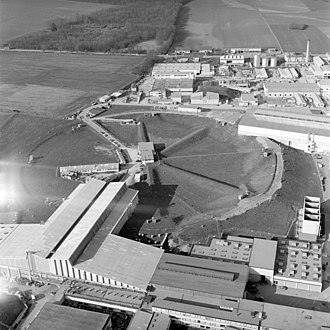 Proton Synchrotron - Aerial view of the 28 GeV Protron Synchrotron. The underground ring of the 28 GeV proton synchrotron in 1965. Left, the South and North experimental halls. Top right, part of the East hall. Bottom right, the main generator room and the cooling condensers.