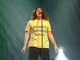 "A man standing behind a microphone stand, wearing a yellow shirt that contains the text ""Atlantic Records Sucks"""