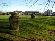 Two standing stones and wooden pilings sitting in a landscaped space surrounded by a modern housing estate