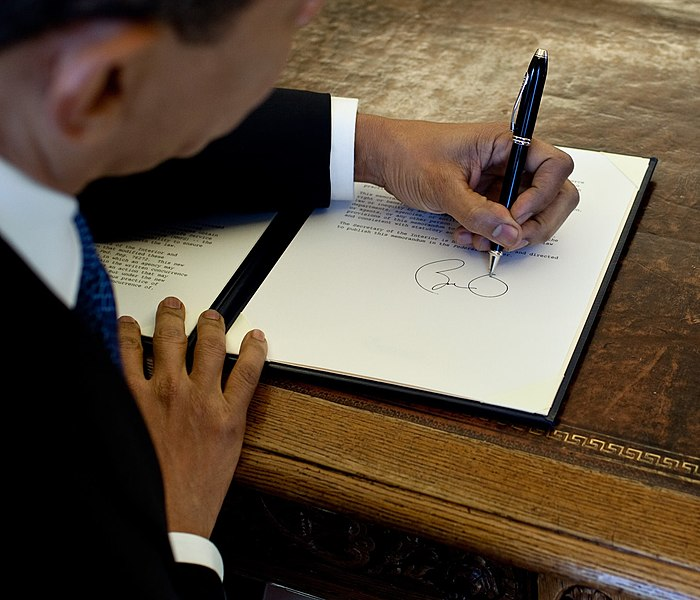 File:Barack Obama signs at his desk2.jpg