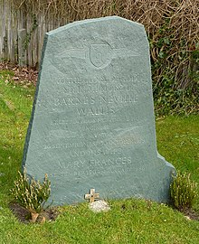 Irregular green gravestone standing in a grassy churchyard