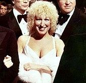 Una mujer con cabello rizado rubio con un vestido blanco y un chal de piel, rodeada de hombres con esmoquin