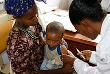 A woman holds a baby while another woman prepares to inject a vaccine.